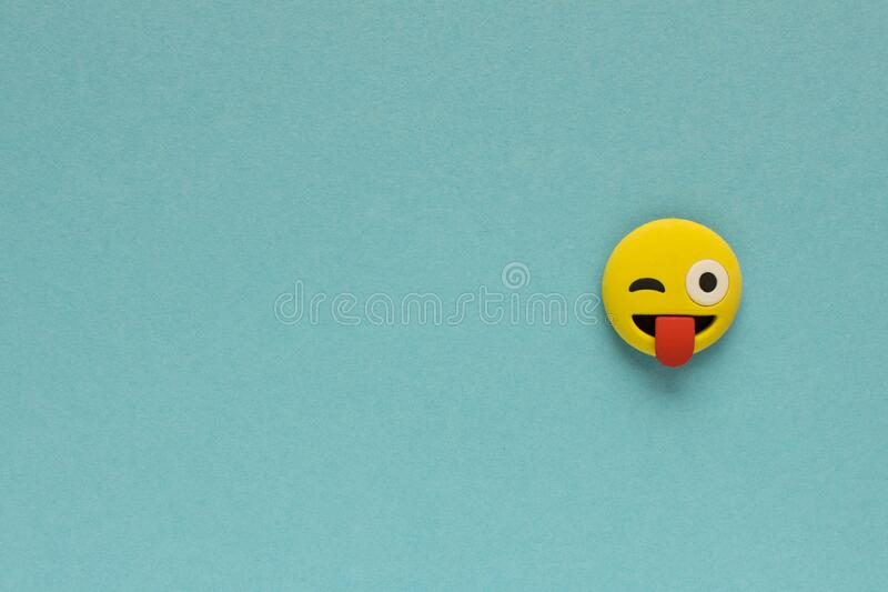 Yellow funny smiley face on blue background. Positive mood concept.  stock photos
