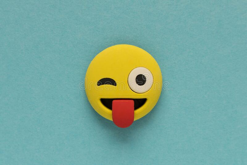 Yellow funny smiley face on blue background. Positive mood concept.  royalty free stock photo