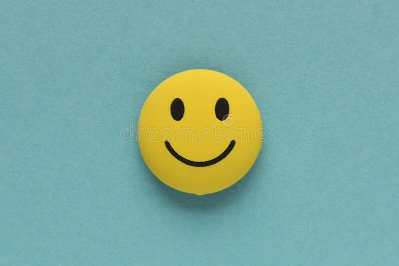 Yellow funny smiley face on blue background. Positive mood concept.  royalty free stock images