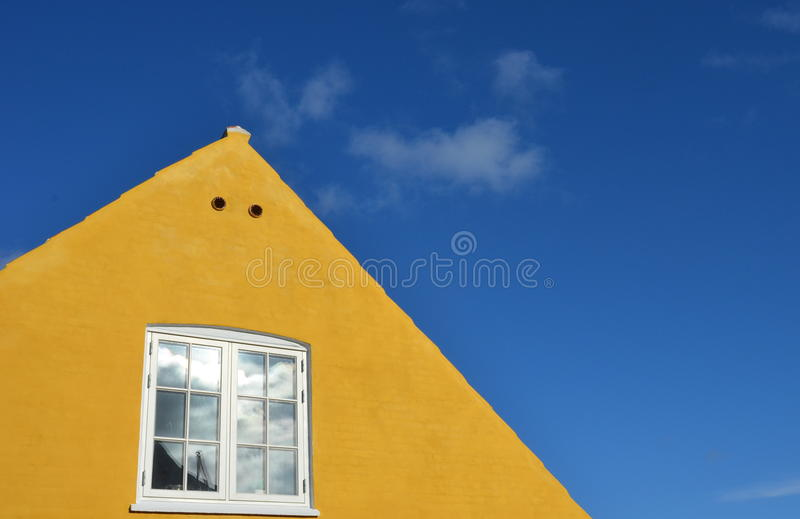 Yellow gable with white window royalty free stock photo