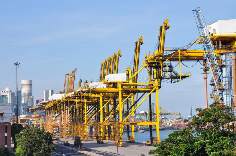 Yellow gantry cranes. A gantry crane has a hoist in a fixed machinery house or on a trolley that runs horizontally along rails, usually fitted on a single beam ( stock image