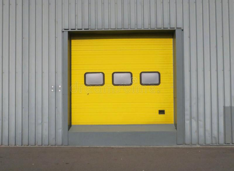 Yellow garage door with three windows in a grey metal wall. A yellow garage door with three windows in a grey metal wall stock photos
