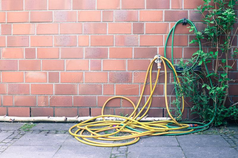 Yellow garden hose wrapped on a house royalty free stock photo