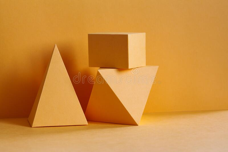 Yellow geometrical platonic solids figures still life composition, simplicity concept. Three-dimensional prism pyramid stock photo