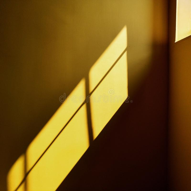 Yellow wall with shadow and sunshine from window. Yellow geometry concept royalty free stock photo