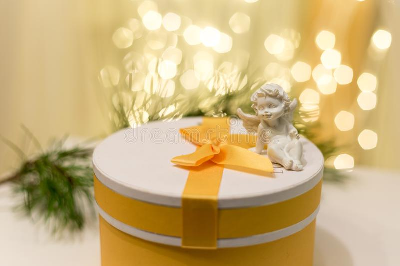 Yellow gift box with lights in the background and an angel on it royalty free stock images