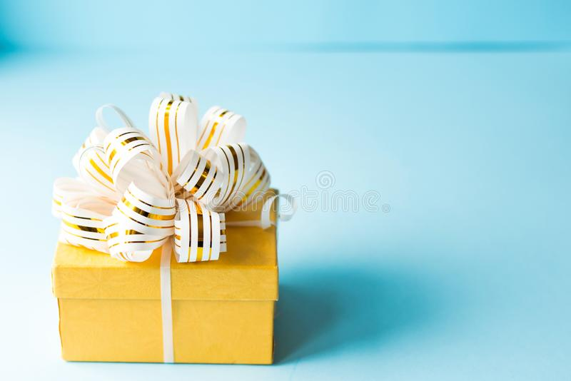Yellow Gift box wrapped in white and gold striped ribbon on blue background. Empty note tied over. copy space . place for text. stock image
