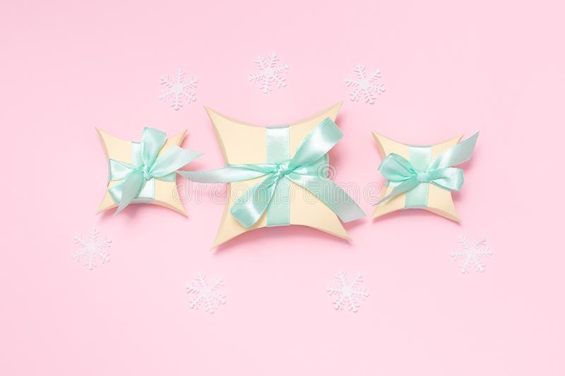 Yellow gift boxes with light green ribbon and white snowflakes on the pink background, flat lay. Social media, winter, christmas stock photo