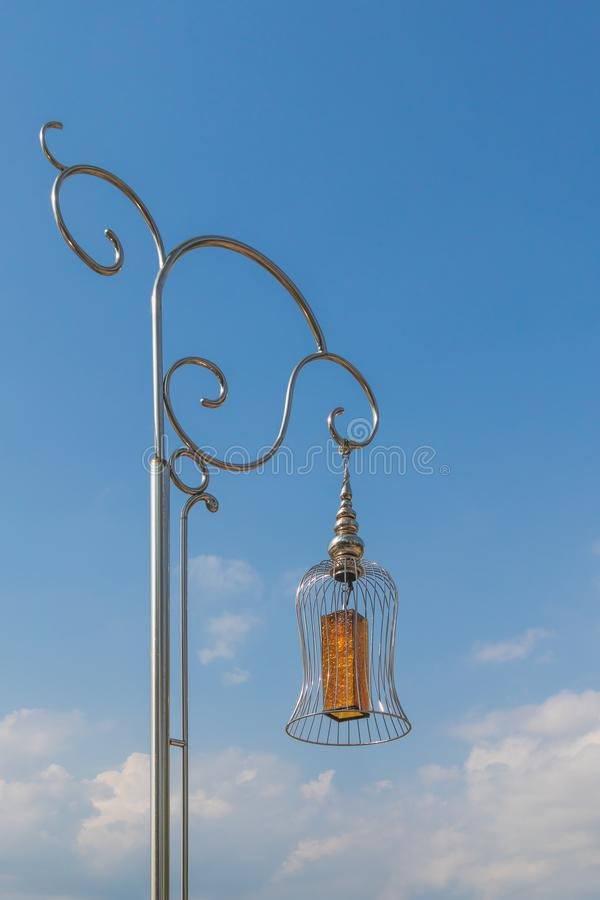 A yellow glass lamp hang up the strong street stainless lamp that the sun reflect in stainless under blue sky with clouds before s. Unset stock images