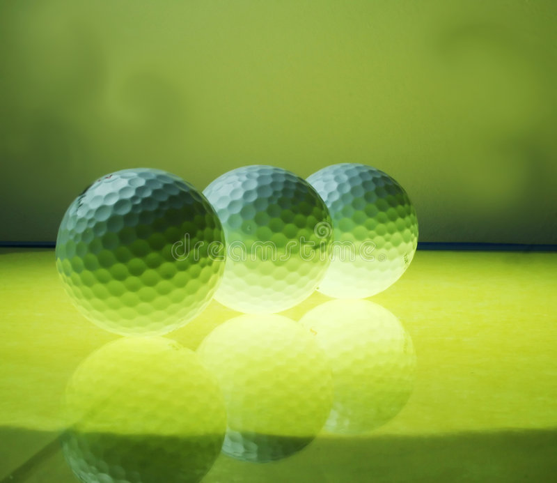 The yellow glow from below gives a magical look. A trio of golf balls glowing on the glass stock photos