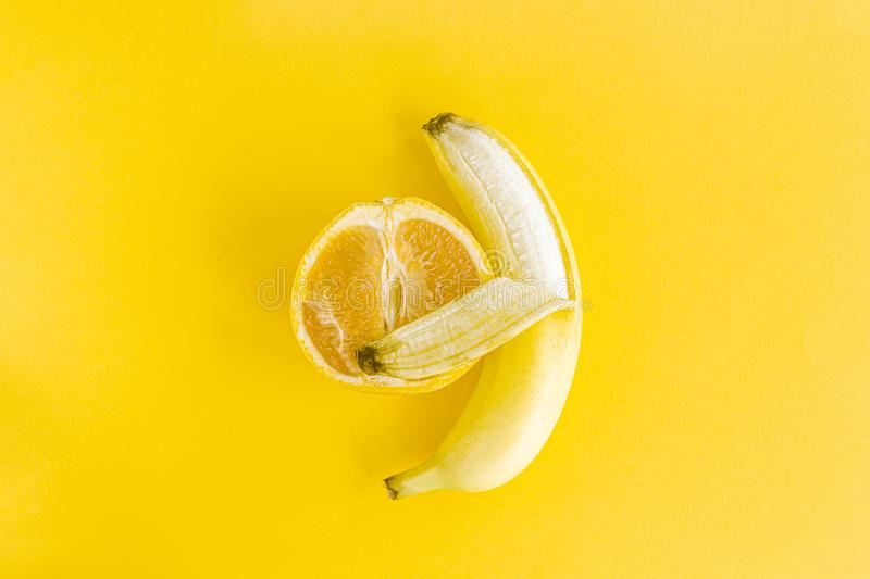 Yellow glowing Banana hugs grapefruit, a creative concept of interracial love, tenderness, warmth, happiness and family lives royalty free stock photos