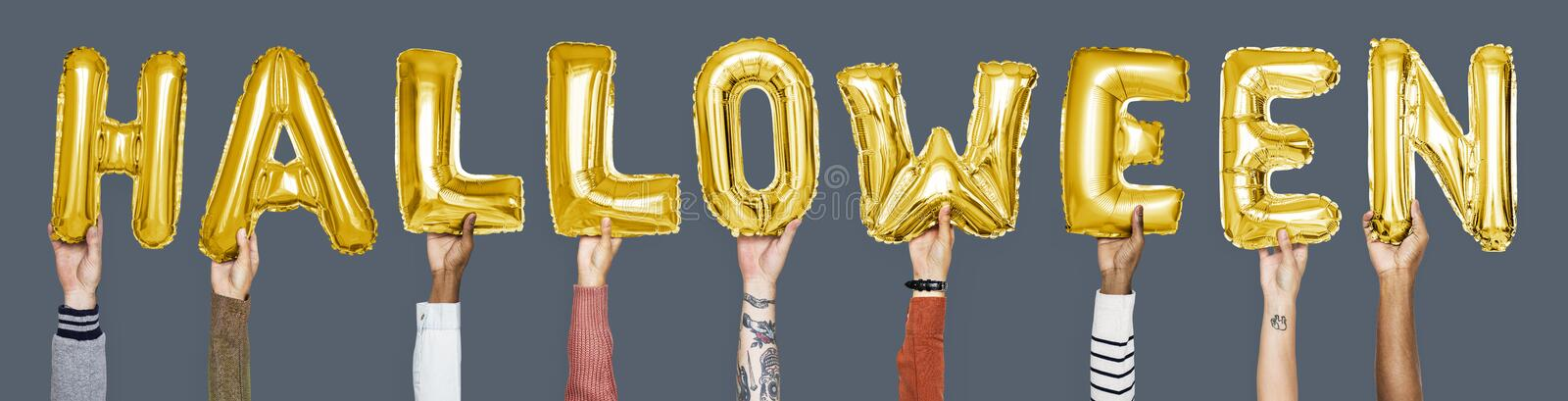 Yellow gold alphabet balloons forming the word halloween royalty free stock images