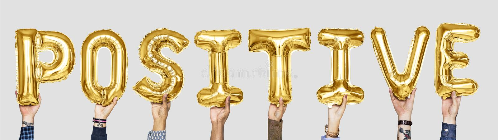 Yellow gold alphabet balloons forming the word positive royalty free stock images