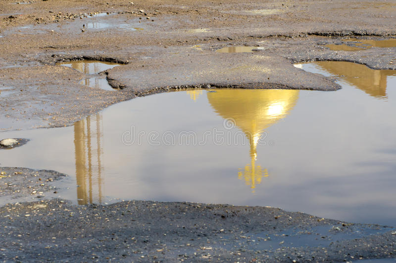 The yellow (gold) dome of the Church with the cross is reflected. In a puddles of bad roads royalty free stock photo