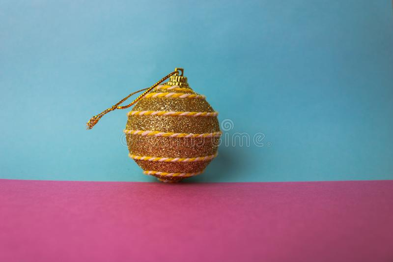 Yellow gold small round xmas festive Christmas ball, Christmas toy plastered over sparkles on a pink purple blue background. Yellow gold small round glass stock images