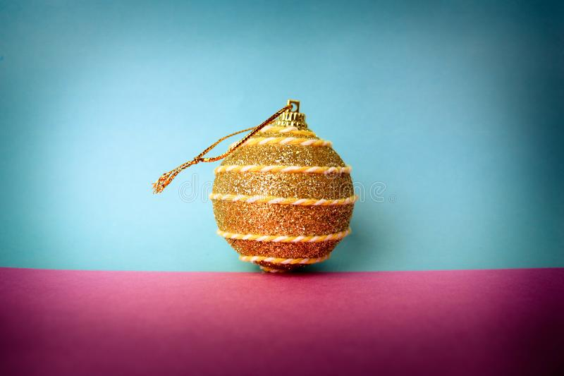 Yellow gold small round xmas festive Christmas ball, Christmas toy plastered over sparkles on a pink purple blue background. Yellow gold small round glass royalty free stock photos