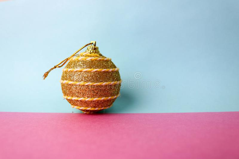 Yellow gold small round xmas festive Christmas ball, Christmas toy plastered over sparkles on a pink purple blue background. Yellow gold small round glass stock photography
