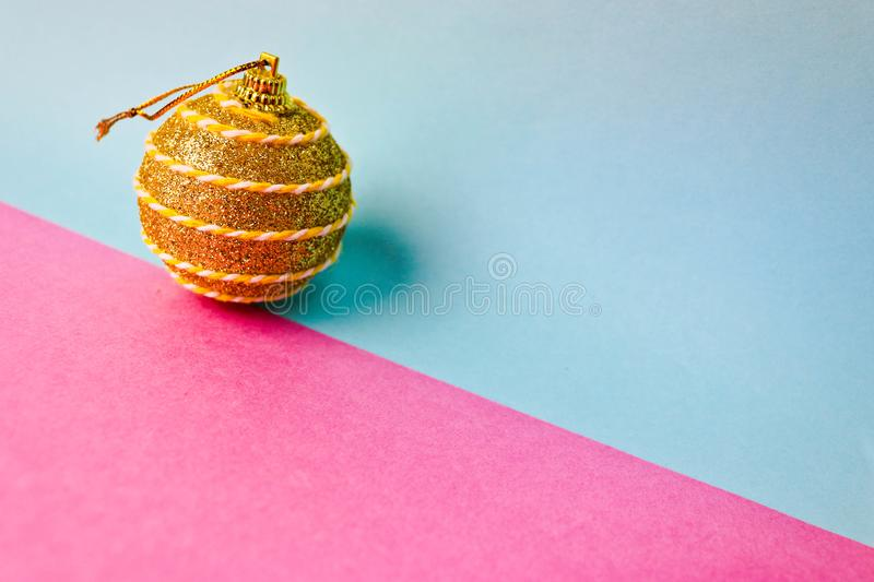 Yellow gold small round xmas festive Christmas ball, Christmas toy plastered over sparkles on a pink purple blue background. Yellow gold small round glass stock photo