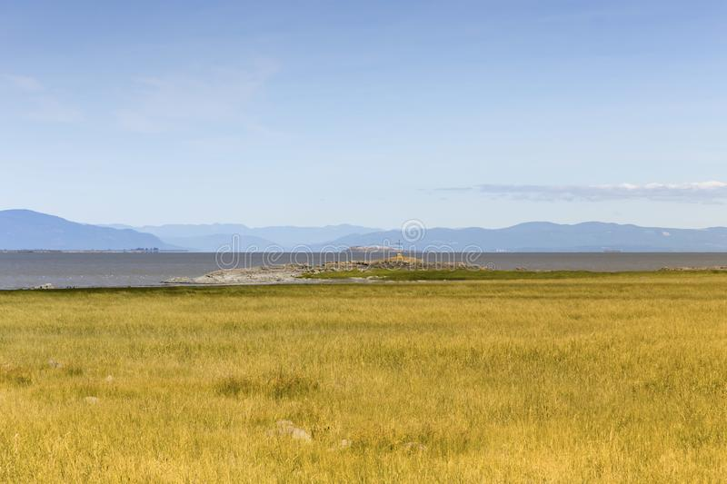 Yellow grass at low tide and iron cross on Panet Rock in L'Islet-sur-Mer with l'Île-aux-Oies and Charlevoix in the background stock photo