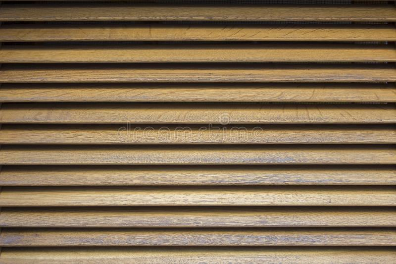 Yellow gray wooden shutters with shadows. horizontal lines. rough surface texture royalty free stock images