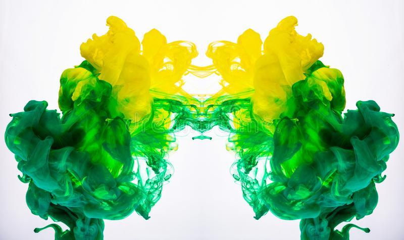 Yellow and green acrylic paint, abstract color clouds underwater. Macro shot of acrylic pigment blending in liquid. Two. Ink colours mixing in water, isolated royalty free stock photos