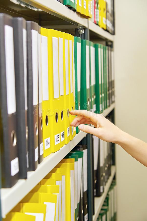 Yellow, green and black file folders in archive and human hand pointing on them. Yellow, green and black file folders in archive and human hand pointing on them stock images
