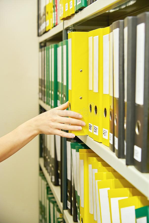 Yellow, green and black file folders in archive and human hand pointing on them. Yellow, green and black file folders in archive and human hand pointing on them royalty free stock photo