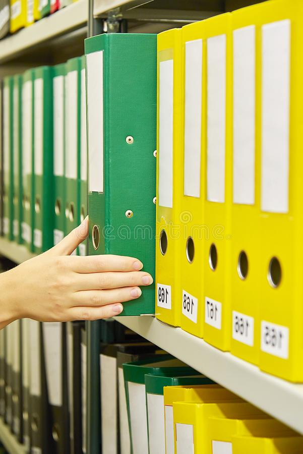 Yellow, green and black file folders in archive and human hand pointing on them. Yellow, green and black file folders in archive and human hand pointing on them stock photo