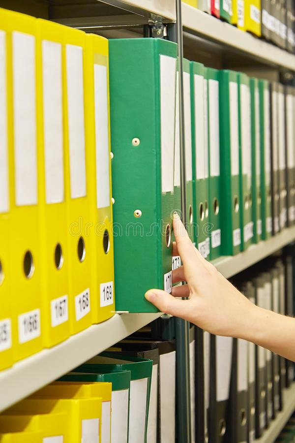 Yellow, green and black file folders in archive and human hand pointing on them. Yellow, green and black file folders in archive and human hand pointing on them stock image