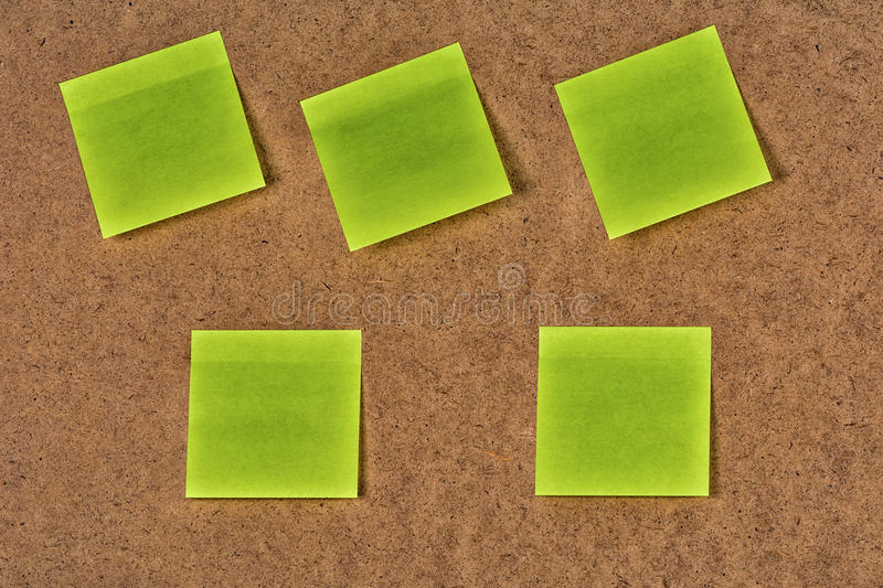 Yellow-green blank paper stickers on the old fibrous cardboard stock image