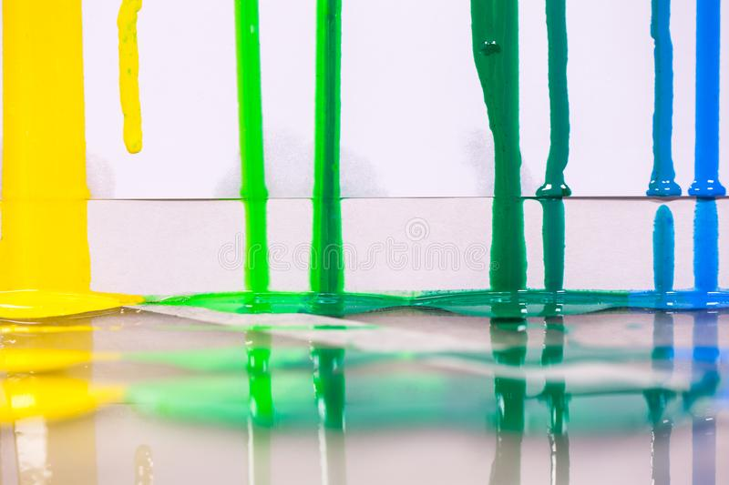 Yellow green and blue of screen print colors are dripping. In white background stock images