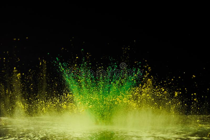 Yellow and green holi powder explosion on black royalty free stock photos