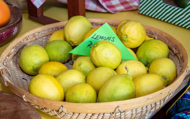 Yellow and green lemons in a woven basket stock photos