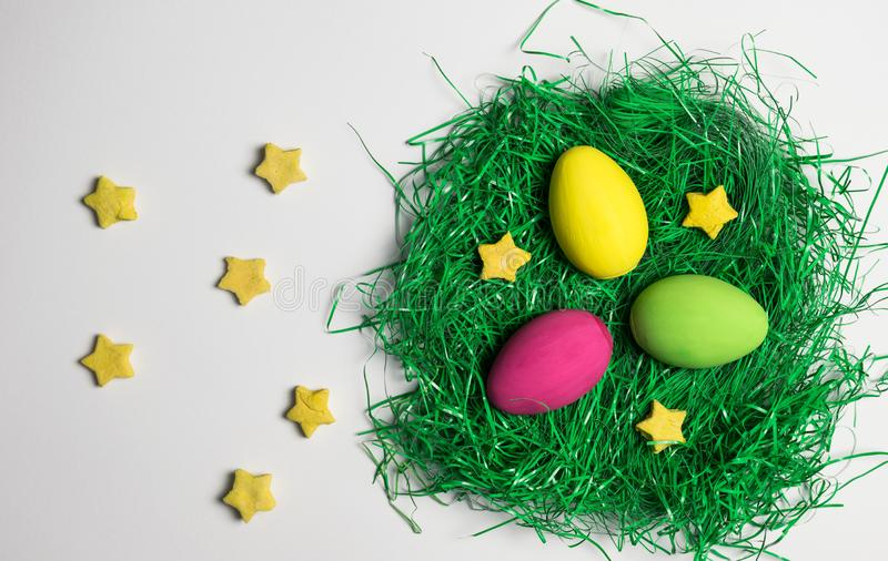 Yellow, green and pink Easter egg in nest of artificial green grass with yellow decorative stars all over white background. Easter eggs, yellow, pink and green royalty free stock images