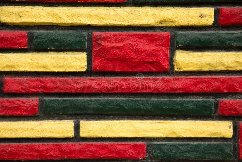 Yellow, green and red peint brick wall royalty free stock photos