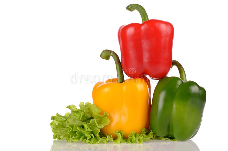 Yellow Green and Red peppers on salad leaf isolated on white background stock photos