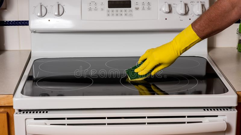 Main uses sponge to clean a stovetop in the kitchen royalty free stock photos