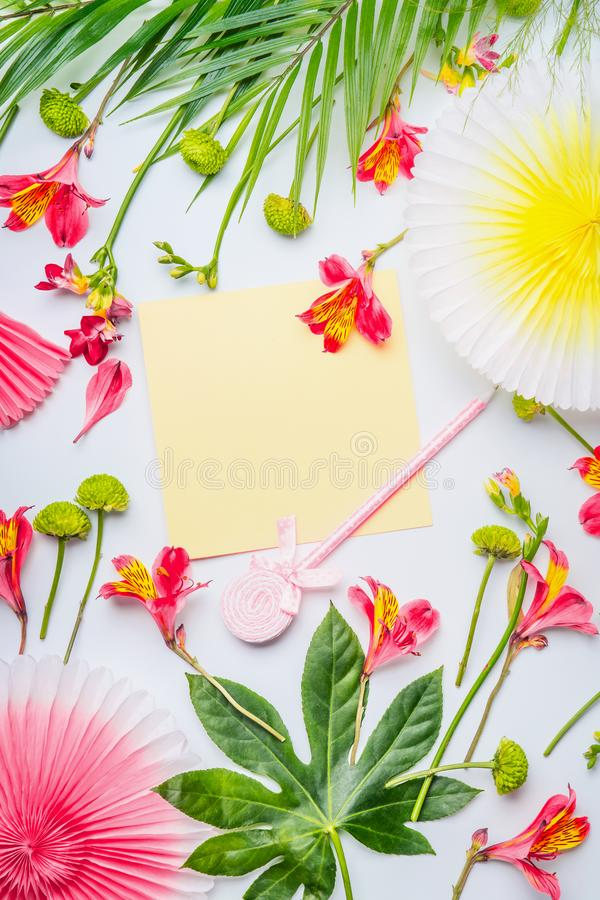 Yellow greeting card mock up with paper party fans, tropical leaves and flowers on white background, top view. Vertical. Flat lay stock image