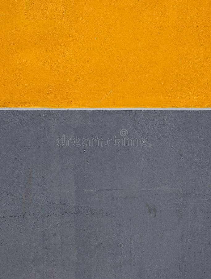 Yellow and grey areas of paint on a rough textured concrete wall divided by a horizontal white stripe royalty free stock image