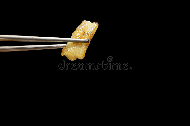 yellow grilled pork fat between silver chopsticks on black background royalty free stock image