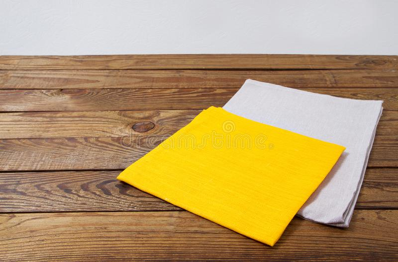 Yellow and grow napkins on old wooden table, food drink concept, mock up.  stock photography