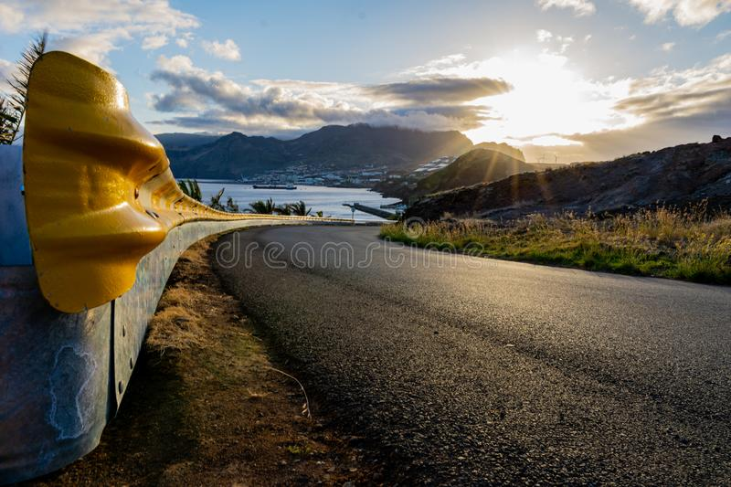 Yellow guardrail along curvy road with sunset over the sea and village stock images