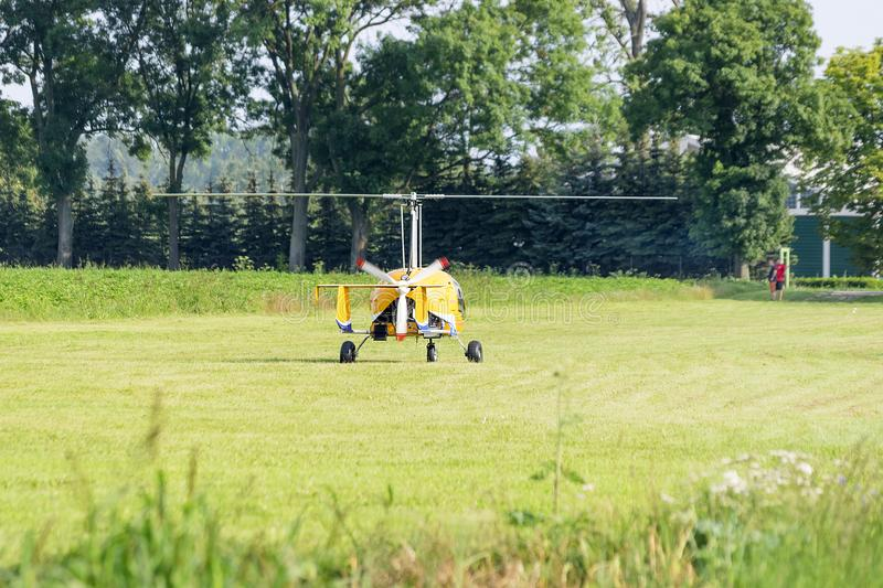 Yellow gyrocopter standing on a meadow stock photo