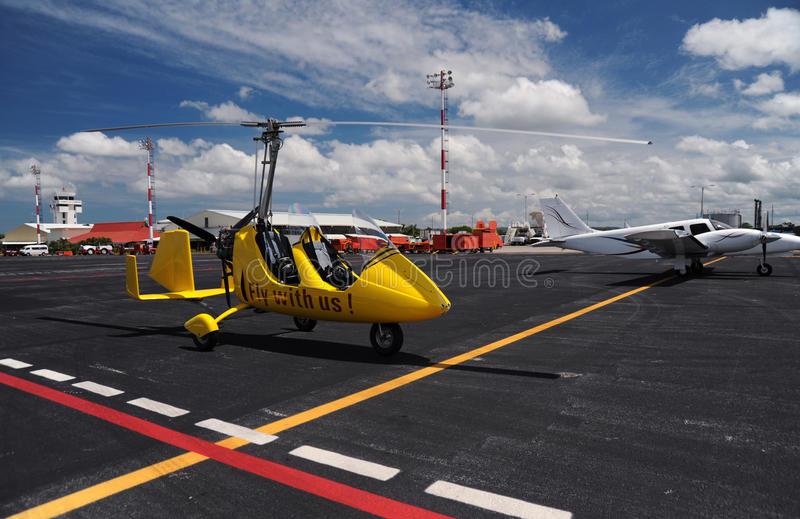 Yellow gyroplane in the international airport stock image