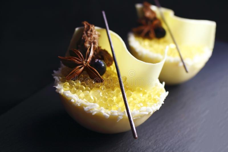 Yellow half sphere lemon jelly caviar and white melon mousse dessert with coconut, honey, white chocolate and star anise stock photo