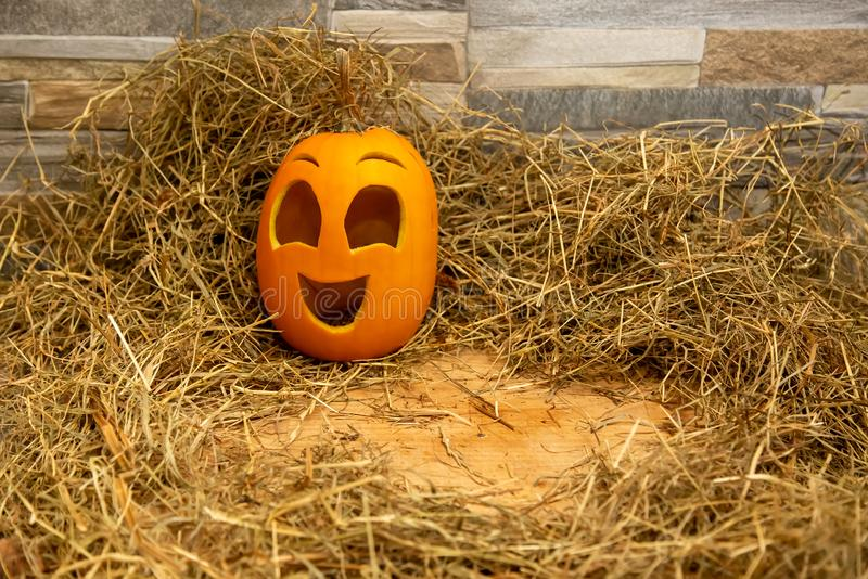 Yellow and happy smiling pumpkin. Halloween symbol on a gray stone wall background, stands on a hay and a wooden stand. Jack o. Lantern and copy space royalty free stock photography