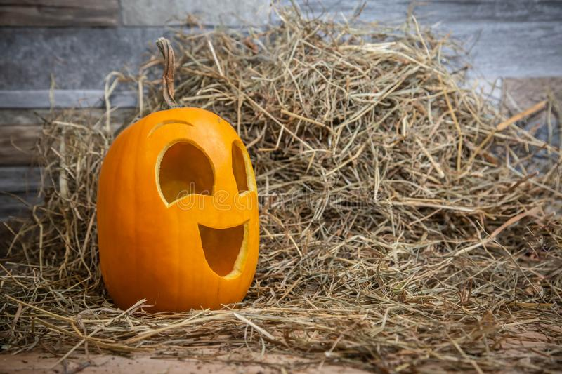 Yellow and happy smiling pumpkin. Halloween symbol on a gray stone wall background, stands on a hay and a wooden stand.  stock photography