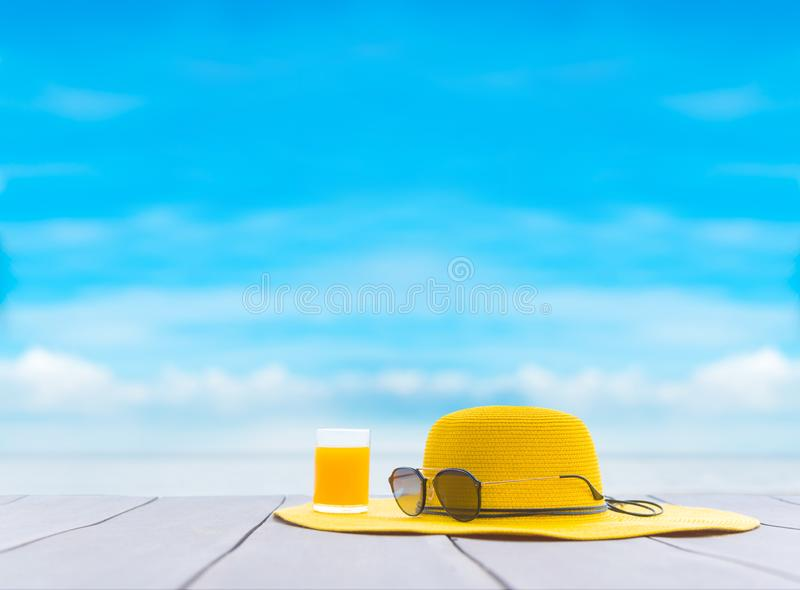 Yellow hat with fresh orange juice on the beach. royalty free stock photography
