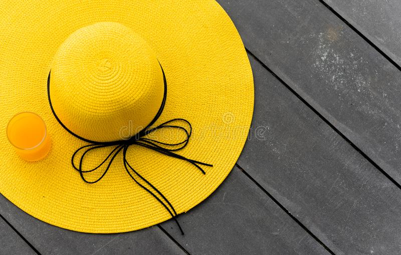 Yellow hat with fresh orange juice on the beach. Summer vacation with space on wood background royalty free stock photography