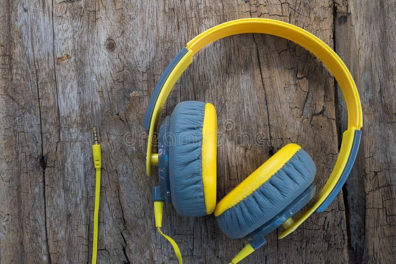 Yellow headphone. On wood backdround stock photos